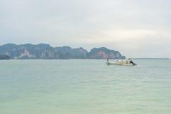 Barco viejo de la cola larga en el mar con el fondo de la montaña Fotografía de archivo