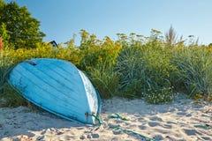 Barco viejo en una playa entre las flores imagen de archivo libre de regalías