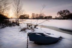 Barco viejo Nevado cerca del río congelado el tiempo de la puesta del sol Imágenes de archivo libres de regalías