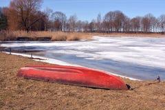 Barco viejo rojo en costa y el hielo tempranos del lago Imagen de archivo