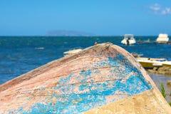 Barco viejo vuelto hacia arriba en el mar imagenes de archivo