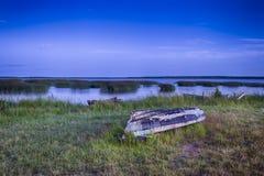 Barco volcado en la superficie cercana de tierra del agua en los lagos bielorrusos Braslav del parque nacional Fotos de archivo