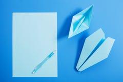 Barco y aviones de papel en fondo del papel azul Fotos de archivo libres de regalías