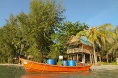 Barco y casa de planta baja en las orillas del mar Imagenes de archivo