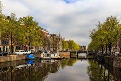 Barco y casa flotante en el canal en Amsterdam Imagen de archivo libre de regalías