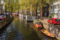 Barco y casa flotante en el canal en Amsterdam Fotografía de archivo