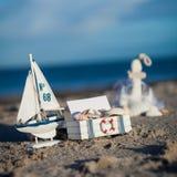 Barco y concha marina de navegación en primer de la decoración de la arena Fotos de archivo
