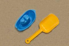 Barco y cuchilla plásticos del juguete en la arena Imagenes de archivo
