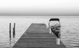 Barco y embarcadero en la salida del sol blanco y negro fotografía de archivo libre de regalías
