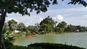 Barco y embarcadero rojos por un lago en un parque Imagen de archivo libre de regalías