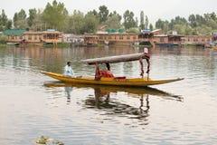 Barco y gente india en el lago Dal Srinagar, la India Foto de archivo libre de regalías