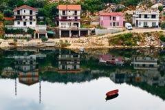 Barco y la aldea en la orilla del lago Fotografía de archivo libre de regalías