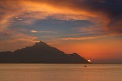 Barco y montaña hacia el sol en el amanecer Fotos de archivo