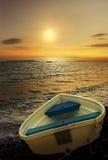 Barco y puesta del sol de rowing viejo. Imagen de archivo