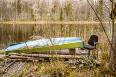 Barco y silla en la costa del lago salvaje fotos de archivo