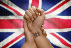 Barcode ID number on wrist of dark skinned person and national flag on background - United Kingdom Stock Photos