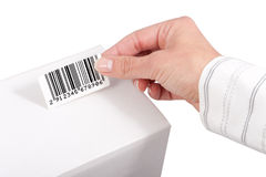 Barcode label. Sticking barcode label on white box stock photos