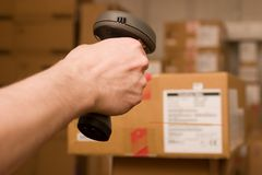 Barcode scaner in hands for a man. A man gets on the hip scaner in operations directed on printed barcode. Warehouse scene Royalty Free Stock Images