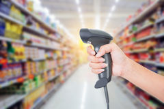Barcode scanner. In woman hand isolated on supermarket background Stock Image