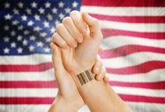 Barcodelegitimationnummer på handleden och nationsflaggan på bakgrund - Förenta staterna arkivbilder
