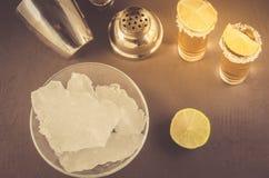 Barconcept: Tequilaschoten, kalk, ijs en schudbeker/Tequila-schoten, kalk, ijs en schudbeker op een donkere achtergrond Hoogste m stock foto