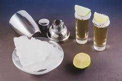 Barconcept: Tequilaschoten, kalk, ijs en schudbeker/Tequila-schoten, kalk, ijs en schudbeker op een donkere achtergrond Selectiev royalty-vrije stock afbeeldingen