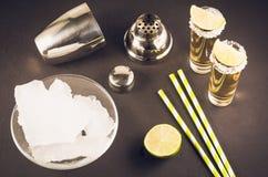 Barconcept: Tequilaschoten, kalk, ijs, stro en schudbeker/Tequila-schoten, kalk, ijs, stro en schudbeker op een donkere achtergro royalty-vrije stock fotografie