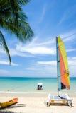 Barcos agradables en la playa con la arena agradable y el cielo azul del claro con las nubes y el árbol de coco blancos Imágenes de archivo libres de regalías