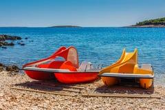 Barcos amarelos e vermelhos do catamarã do pedal com corrediça em uma costa de mar o Imagem de Stock