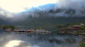Barcos amarrados e cabana vermelha perto da vila de Reine video estoque