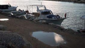Barcos amarrados en bahía cerca de orilla rocosa almacen de metraje de vídeo