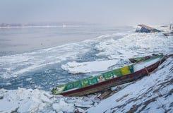 Barcos atrapados en el banco del río congelado Danubio Fotografía de archivo