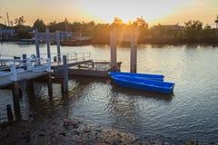 Barcos azules amarrados con el embarcadero en el lado en el canal por la tarde Foto de archivo