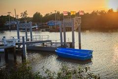 Barcos azules amarrados con el embarcadero en el lado en el canal por la tarde Imágenes de archivo libres de regalías