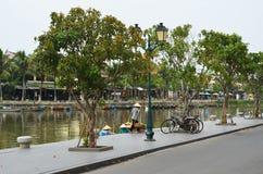 Barcos, bicicletas e mulheres por um rio em Hoi An, Vietname Fotos de Stock Royalty Free