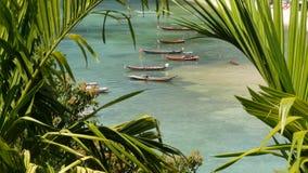 Barcos cerca de la orilla de la isla Barcos pesqueros coloridos tradicionales que flotan en el agua azul tranquila cerca de la co almacen de metraje de vídeo