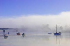 Barcos coloridos en un río brumoso Fotos de archivo libres de regalías