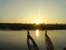 Barcos con el parque nacional Nepal de Chitwan de la puesta del sol Fotografía de archivo