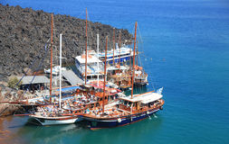 Barcos da excursão do turista no porto pequeno no vulcão de Santorini Foto de Stock