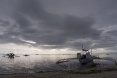 Barcos de Banca bajo amenazar a los cielos tempestuosos, isla de Panglao, Bohol, Filipinas Imagenes de archivo