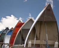 Barcos de enfileiramento alinhados verticalmente de encontro ao céu azul Imagem de Stock Royalty Free