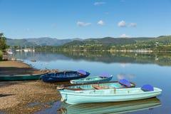 Barcos de enfileiramento para o aluguer para o prazer e o lazer pelo lago e por montanhas bonitos no dia da calma ainda Imagens de Stock Royalty Free