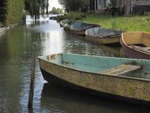 Barcos de enfileiramento velhos para o aluguer em um canal holandês foto de stock