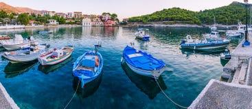 Barcos de Fisher na âncora na baía do mar da vila de Assos na angra bonita dos azuis celestes em Kefalonia, Grécia Imagem de Stock Royalty Free