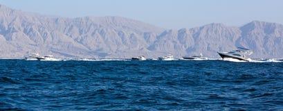 Barcos de la velocidad que cruzan cerca de las montañas Fotos de archivo