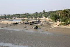 Barcos de los pescadores trenzados en el fango durante la bajamar en la ciudad de enlatado cercana de Malta del río, la India Fotos de archivo
