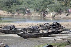 Barcos de los pescadores trenzados en el fango durante la bajamar en la ciudad de enlatado cercana de Malta del río, la India Foto de archivo libre de regalías