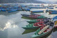 barcos de madeira coloridos no lago contra o contexto de montanhas verdes barcos vazios amarelos verdes vermelhos azuis na água fotos de stock royalty free