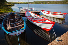 Barcos de madeira de flutuação da cor com pás em um lago Imagens de Stock Royalty Free