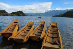Barcos de madeira tradicionais que flutuam no lago Lugu, Yunnan, China Imagens de Stock